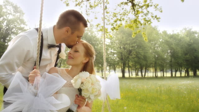slo mo bride and groom kissing on a swing in nature - swinging stock videos & royalty-free footage