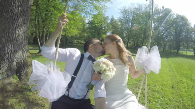 POV Bride and groom kissing on the swing in sunshine