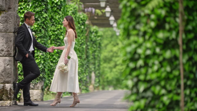slo mo bride and groom meeting in an ivy covered passageway - bunch of flowers stock videos and b-roll footage