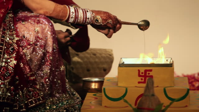 bride and groom pouring ghee into havan kund  - butter stock videos and b-roll footage