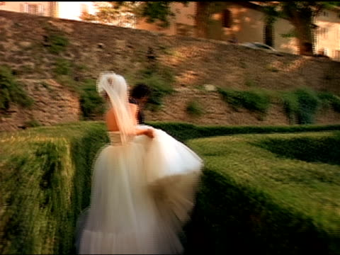 a bride and groom run together through a maze. - bride stock videos and b-roll footage