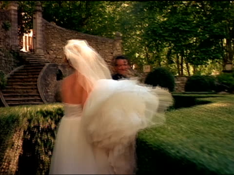 A bride and groom run together through a maze.