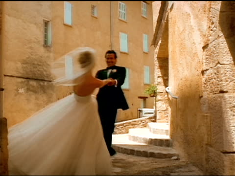 a bride and groom smile as they hold hands and spin. - dinner jacket stock videos & royalty-free footage