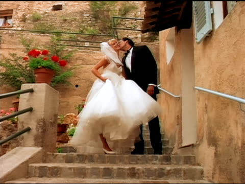 a bride and groom smile as they run down stone steps. - dinner jacket stock videos & royalty-free footage