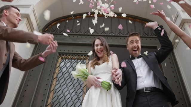 slo mo bride and groom stepping out of the church - married stock videos & royalty-free footage