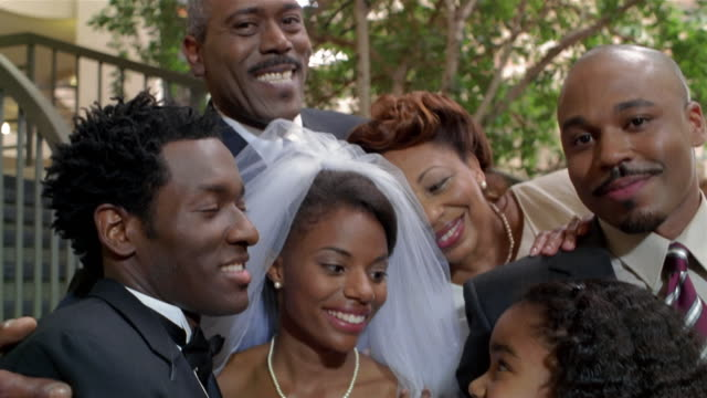 Bride and groom surrounded by family after wedding