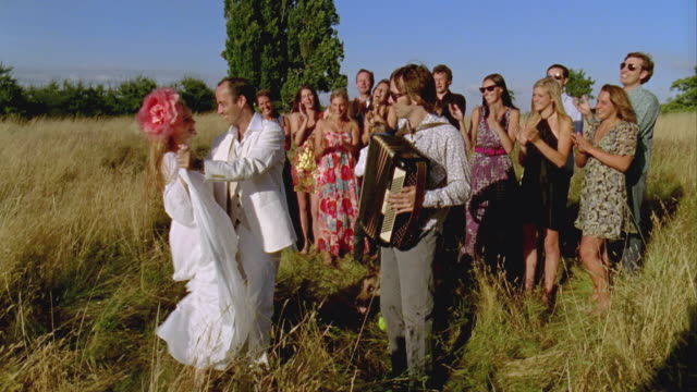 WS, Bride and groom surrounded with wedding guests dancing in field, Saint Ferme, Gironde, France