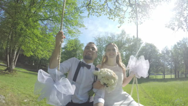 pov bride and groom swinging under a tree in sunshine - life events stock videos & royalty-free footage