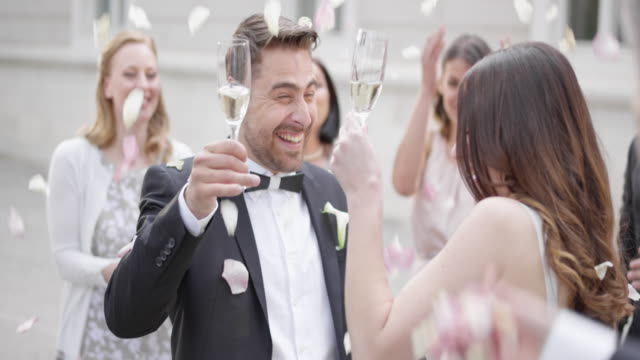 slo mo bride and groom toasting in a rose petal shower - wedding stock videos and b-roll footage