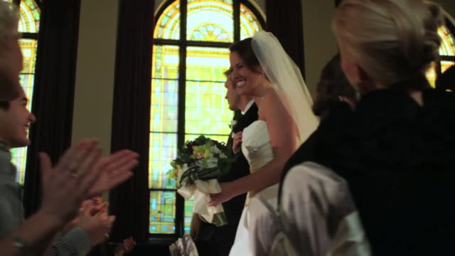 TS bride and groom walk down aisle together
