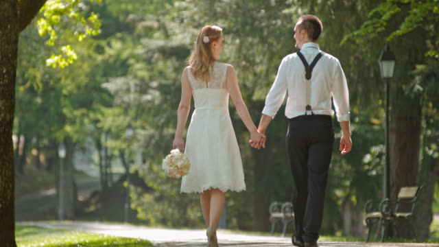 SLO MO Bride and groom walking and holding hands