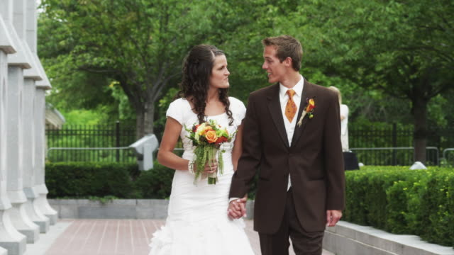 ms pan bride and groom walking and kissing in garden / salt lake city, utah, usa - groom stock videos and b-roll footage