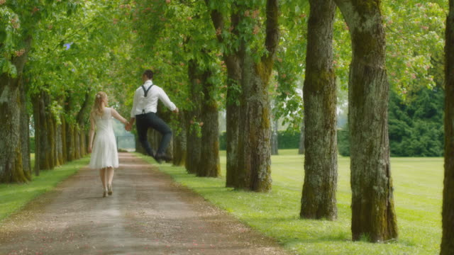 slo mo ds bride and groom walking down the avenue - wedding dress stock videos & royalty-free footage