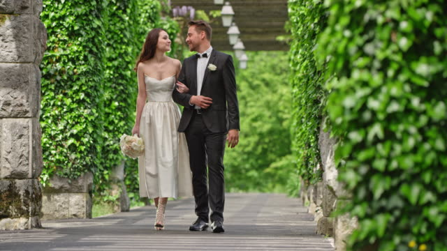 SLO MO Bride and groom walking trough a romantic passageway