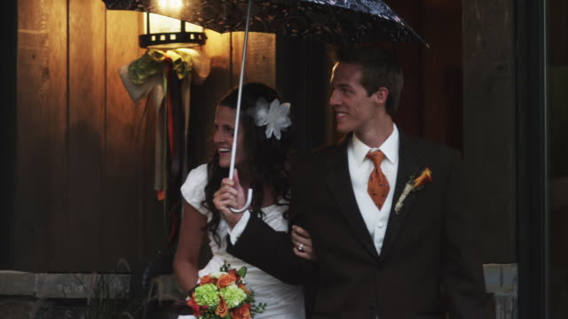 ms pan bride and walking under umbrella / draper, utah, usa - boutonniere stock videos and b-roll footage