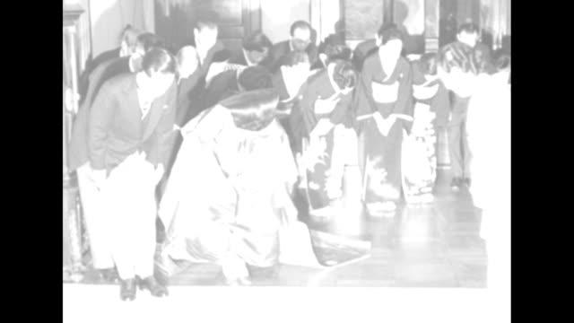 Bride Atsuko Princess Yori and groom Ikeda Takamasa pose and then bow as Atsuko's mother Empress Kojun descends and passes they follow