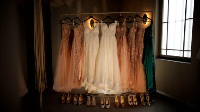 stockvideo's en b-roll-footage met bruid bruidsmeisjes jurken, trouwjurk en schoenen zijn opknoping in de voorkant van het venster voor de ceremonie - avondjurk