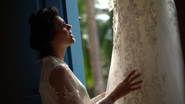 bride checking wedding dress before the wedding ceremony - abito da sposa video stock e b–roll
