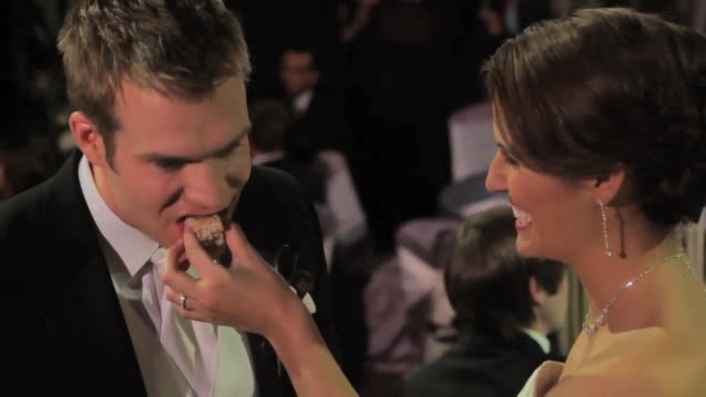 Bride feeds wedding cake to groom