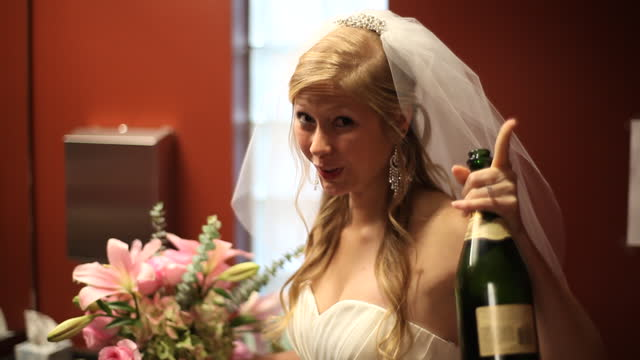 HANDHELD MEDIUM SHOT bride finishes drinking bottle of champagne then turns to camera in bathroom before wedding
