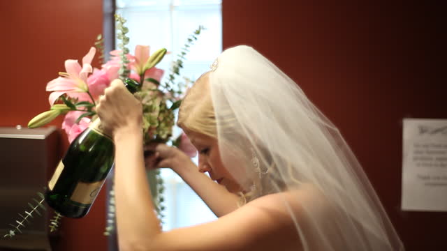 HANDHELD MEDIUM SHOT bride finishes drinking bottle of champagne while raising her bouquet in air then licks her hand in bathroom before wedding
