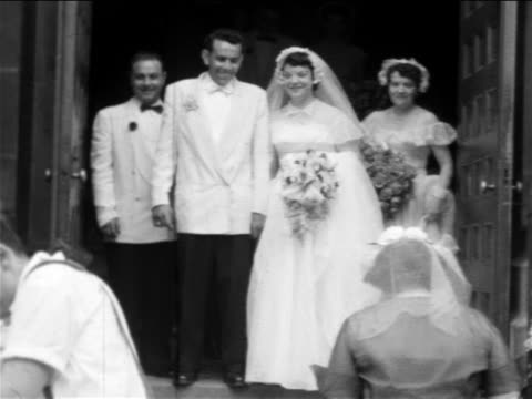 vídeos de stock, filmes e b-roll de b/w 1955 home movie bride + groom emerge from church - bridesmaid