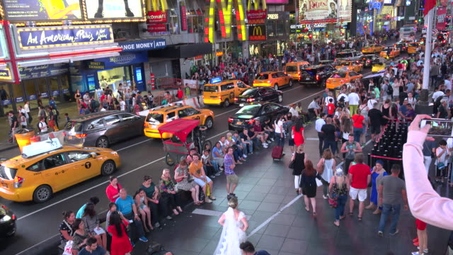 Bride Groom pose for pictures in Duffy Square Times Square / Times Square Midtown Manhattan Broadway and Seventh Avenue 7th Avenue New York City USA