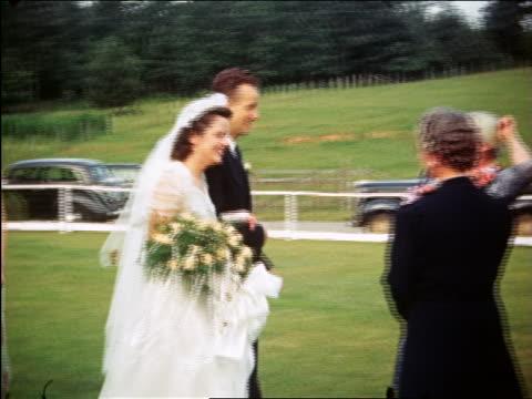vídeos de stock e filmes b-roll de 1940 bride + groom walk toward three senior people outdoors / maplewood, nj / home movie - pai da noiva