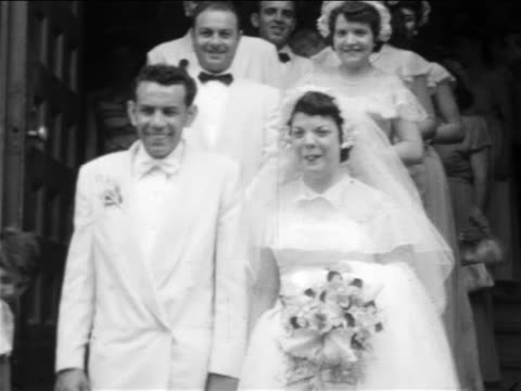stockvideo's en b-roll-footage met b/w 1955 home movie bride + groom + wedding party descend church stairs - 1955