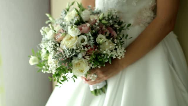 vidéos et rushes de mariée retenant un bouquet de mariage - robe blanche