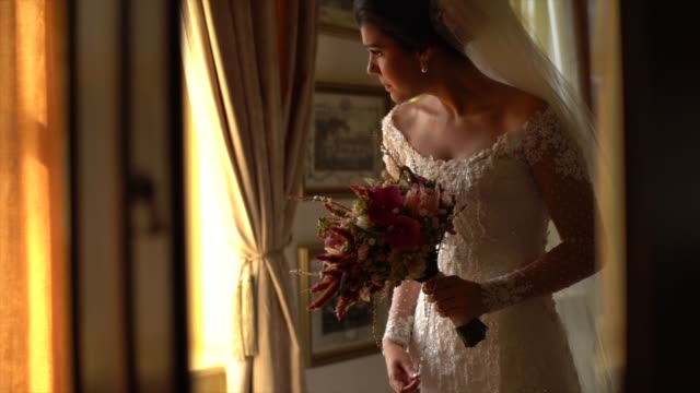 bride holding bouquet and looking through the window before wedding ceremony - christianity stock videos & royalty-free footage