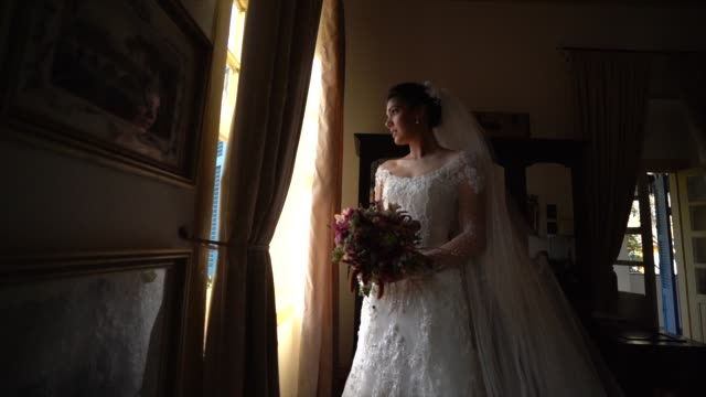 bride holding bouquet and looking through the window before wedding ceremony - bouquet stock videos & royalty-free footage