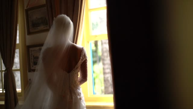 bride holding bouquet and looking through the window before wedding ceremony - bouquet video stock e b–roll