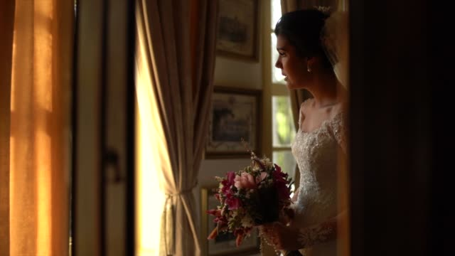 bride holding bouquet and looking through the window before wedding ceremony - anticipation stock videos & royalty-free footage