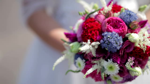 CLOSE UP PANNING SELECTIVE FOCUS Bride holding colorful bouquet