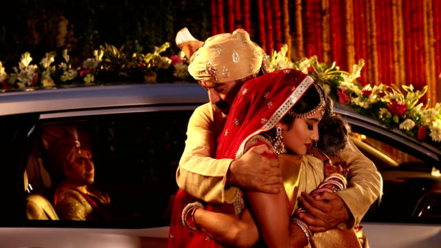 Bride hugging her mother and father, Delhi, India