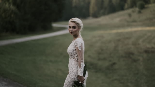bride in a white beautiful dress walking in countryside. - gold dress stock videos & royalty-free footage