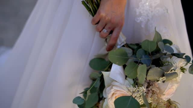 braut in einem weißen hochzeitskleid hält einen blumenstrauß - weißes kleid stock-videos und b-roll-filmmaterial