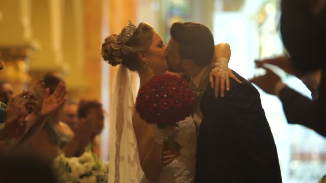 bride kissing the groom in the church - sposa video stock e b–roll