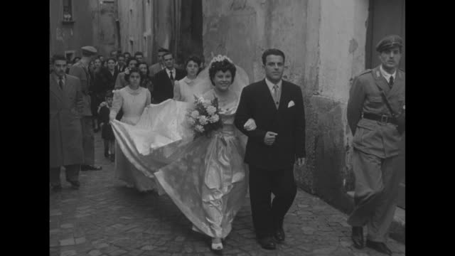 bride nina farano is escorted from a church with a high angle view of a crowd of villagers walking in a narrow street; younger girls carry the train... - married stock videos & royalty-free footage