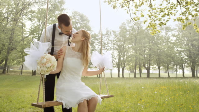 slo mo bride on a swing kissing her groom - married stock videos & royalty-free footage
