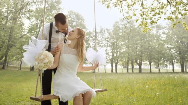 vidéos et rushes de epouse de slo mo sur une balançoire s'embrasser son fiancé - couple marié