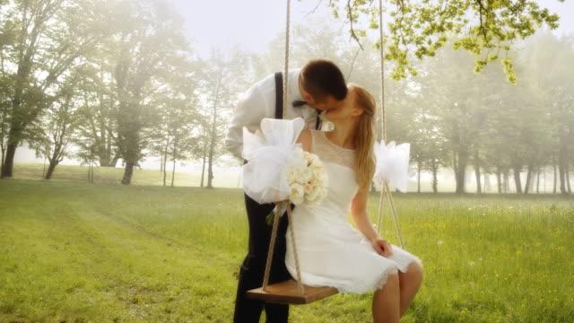 SLO MO CS Bride on a swing kissing the groom