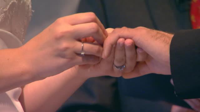 vídeos y material grabado en eventos de stock de bride putting ring on groom's finger - exchanging