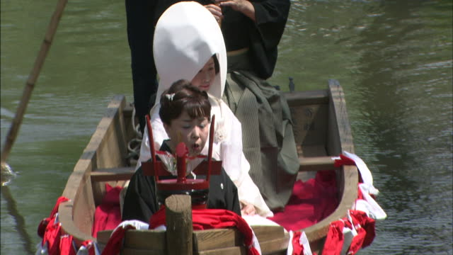 A bride rides in a boat in a wedding procession.