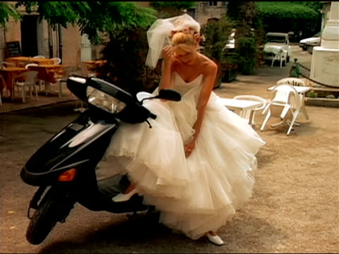 a bride sits on a motor scooter looking sad. - bride stock videos and b-roll footage