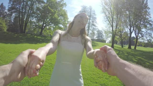 pov braut lächelt und dreht mit dem bräutigam im park - verheiratet stock-videos und b-roll-filmmaterial