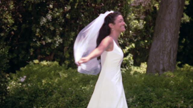 vídeos y material grabado en eventos de stock de slo mo ms bride spinning around in wedding dress / los angeles, california, usa - rotar