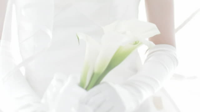 Bride standing holding calla lily