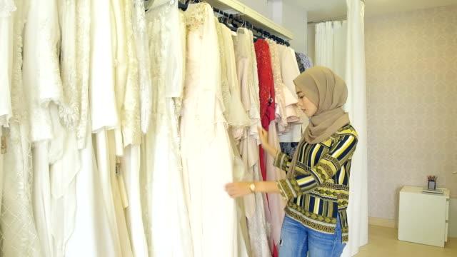 vídeos de stock, filmes e b-roll de uma noiva para ser está escolhendo seu vestido de casamento favoritos - vestuário modesto